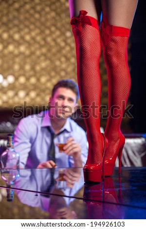 Man watching striptease dancer in red hose. Close up of beautiful legs of strip dancer