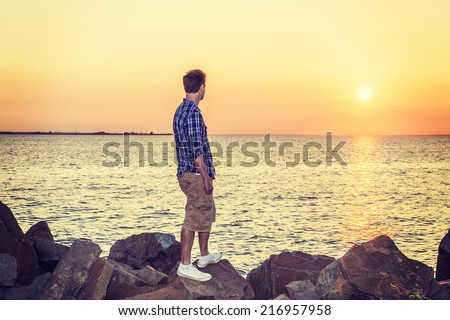 Man Watching Sunset in Back View. Wearing white, blue patterned shirt, yellow pants, white sneakers, a handsome guy is standing on rocks on beach, looking at horizontal of ocean, waiting for you. - stock photo