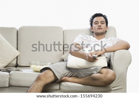 Man watching television on sofa - stock photo