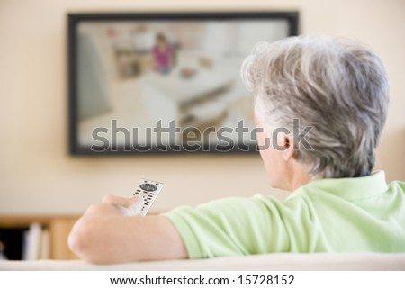 Man watching television using remote control - stock photo