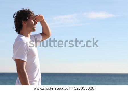 Man watching the sea with his hand in the forehead - stock photo