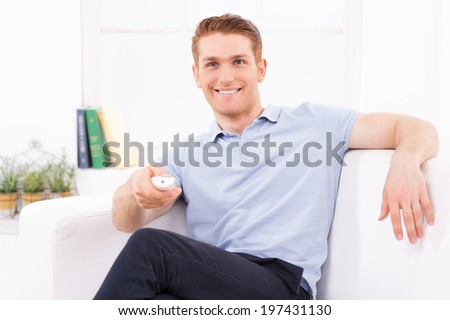 Man watching TV. Handsome young man sitting on the couch and watching TV while holding remote control in hand  - stock photo