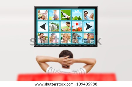 Man watching tv. Photo from behind. Editable copyspace at the screen - stock photo
