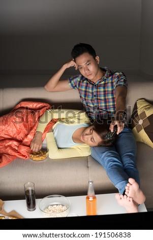 Man watching tv while his girlfriend is sleeping - stock photo