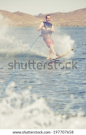 Man water skiing during a hot summer day at the lake. - stock photo