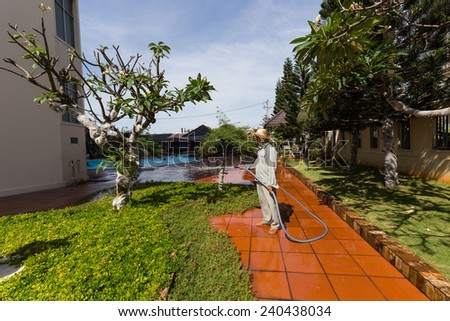 Man watering plant and glass at a garden outside a hotel. - stock photo