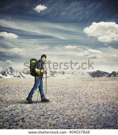 Man wear winter clothes with hiking poles and goggles in the mountains