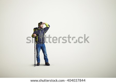 Man wear winter clothes with hiking poles and looking away, on white background - stock photo