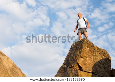 Man wearing a backpack standing on top of a high rock in the summer sunshine looking down at the camera - stock photo