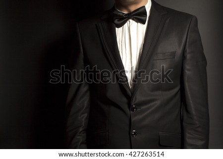 man wearing a black suit and bow tie on black background - stock photo