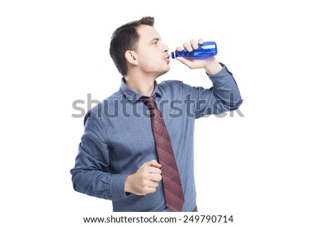 Man wearing a blue shirt and red tie. He is drinking from blue bottle. Over white background - stock photo