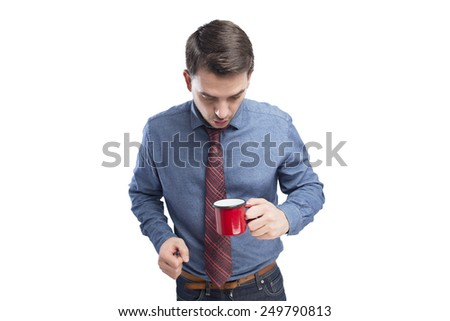 Man wearing a blue shirt and red tie. He is looking surprised into a red cup. Over white background