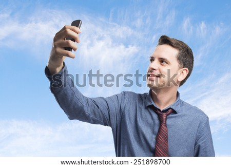 Man wearing a blue shirt and red tie. He is taking a selfie. Over clouds background - stock photo