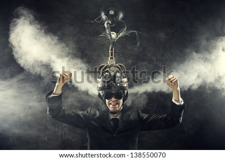 Man wearing a brain-control helmet, celebrating with open arms - stock photo