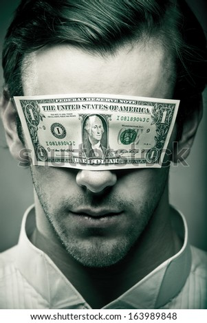 Man wearing a dollar bill as a blindfold.