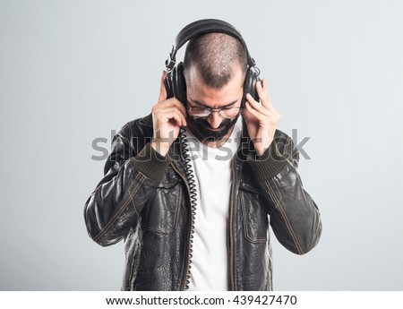 Man wearing a leather jacket listening music over grey background