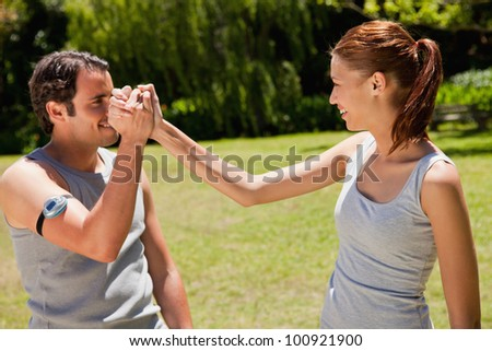 Man wearing a pedometer and a woman smiling as they clasp hands with each other - stock photo