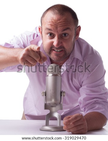 man wearing a pink shirt holding a microphone angry point