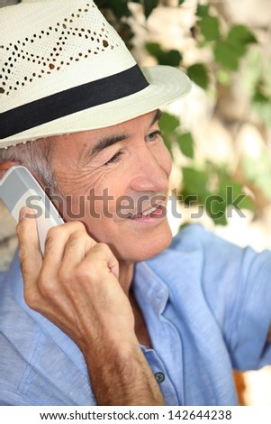 Man wearing a straw hat and talking on his mobile phone - stock photo