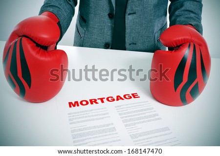 man wearing a suit and boxing gloves with a mortgage contract on his desk - stock photo