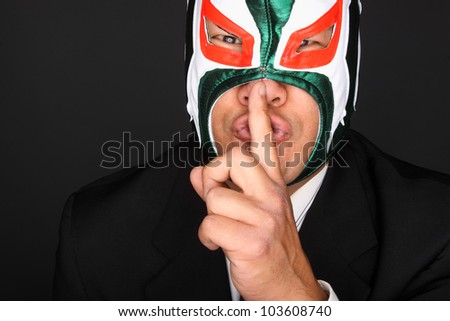 Man wearing a suit and luchador mask making a gesture to be silent.