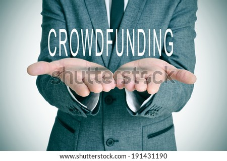 man wearing a suit holding the word crowdfunding in his hands - stock photo