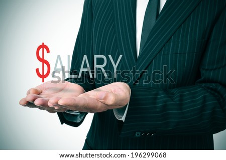 man wearing a suit holding the word salary in his hands - stock photo