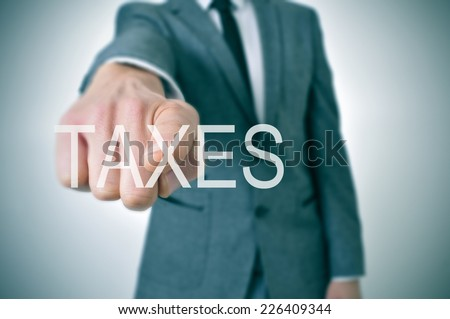 man wearing a suit pointing the finger to the word taxes written in the foreground - stock photo