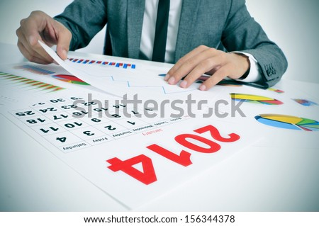 man wearing a suit sitting in a desk observing a pile of charts and with a 2014 calendar in the foreground - stock photo