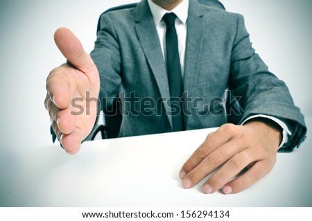 man wearing a suit sitting in a table offering to shake hands - stock photo