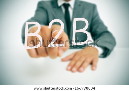 man wearing a suit sitting in a table pointing to the word B2B, business-to-business, written in the foreground - stock photo