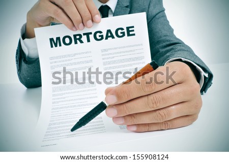 man wearing a suit sitting in a table showing a mortgage loan contract and where the signer must sign - stock photo