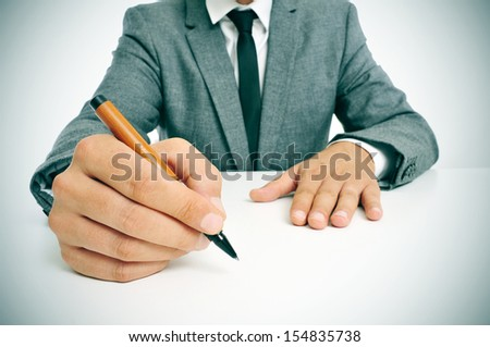 man wearing a suit sitting in a table with a pen in his hand, ready to write, with a blank space