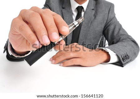 man wearing a suit vaping with an electronic cigarette - stock photo
