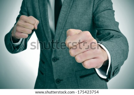 man wearing a suit with ready to fight with his fists - stock photo