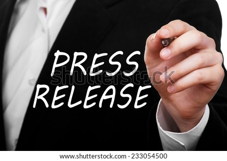 Man wearing a suit writing Press Release concept on transparent glass - stock photo