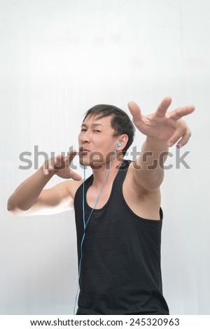 Man wearing a vest black dancing while listening to music with headphones.