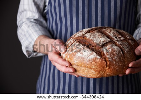 Man Wearing Apron Holding Freshly Baked Loaf Of Bread - stock photo