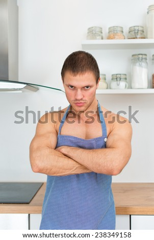 Man wearing apron in the kitchen.