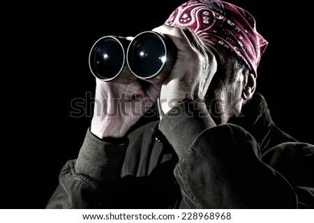 Man wearing bandana, sunglasses and jacket is looking through binoculars - stock photo