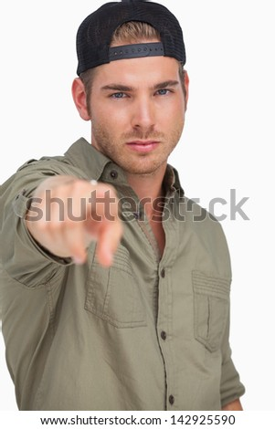 Man wearing baseball hat backwards and pointing on white background - stock photo