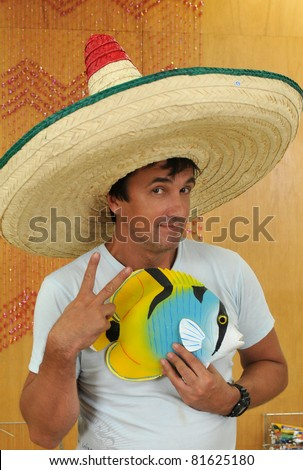 Man wearing big Mexican tri-color sombrero hat  and holding decorative fish - stock photo
