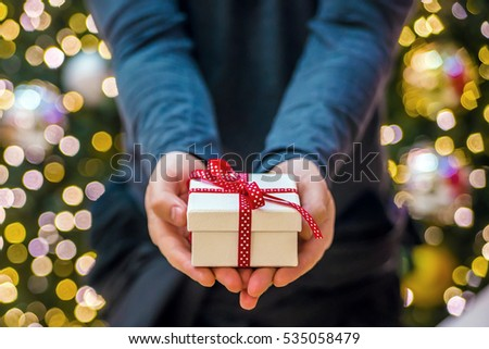 man wearing black shirt holding a christmas gift box. Man holding a gift box, giving someone present. Positive human emotion facial expression feeling attitude life perception