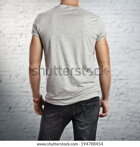 Man wearing blank grey t-shirt. Back - stock photo