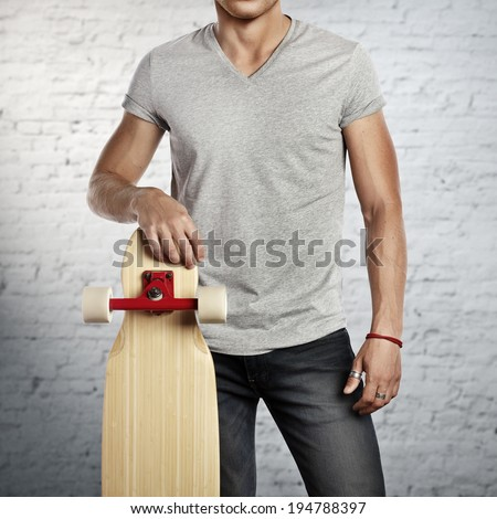 Man wearing blank grey t-shirt holding longboard in his hand