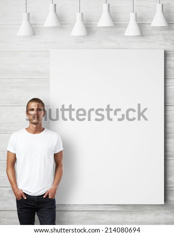 Man wearing blank t-shirt and white poster on a wall - stock photo