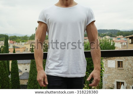 Man wearing blank t-shirt on a city background - stock photo