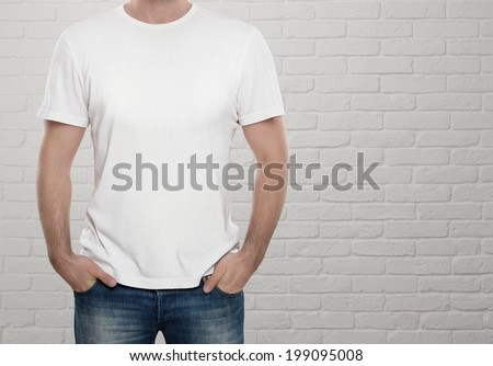 Man wearing blank t-shirt over white brick wall with copy space - stock photo