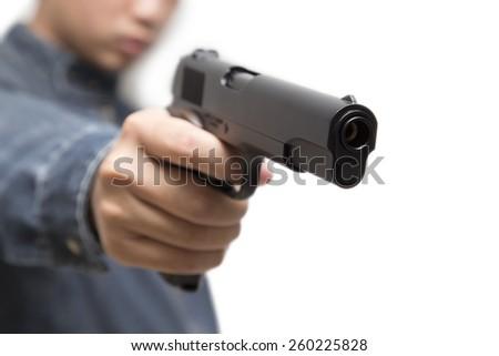Man wearing blue jean jacket aiming gun in hand.  - stock photo