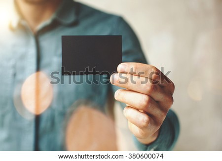 Man wearing blue jeans shirt and showing blank black business card. Blurred background. Horizontal mockup - stock photo